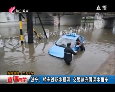 济宁:轿车过积水桥洞 交警趟齐腰深水推车