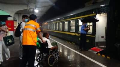 暴雨来袭 兖州火车站冒雨送偏瘫老人上火车